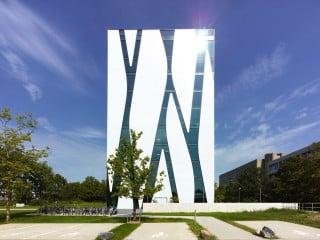 Bibliotheksgebäude mit einer Fassade aus weißem Glasmosaik, auf der sich Fensterbänder gleich Flüssen hinabschlängeln