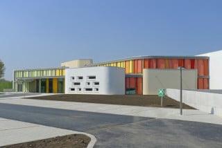 Im organisch geformten Empfangs- und Gemeinschaftsgebäude des Pflegeheims befinden sich die Eingangshalle mit angeschlossener Kapelle, die Bibliothek, der Verabschiedungsraum und die Cafeteria