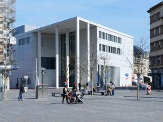 Das Gerichtsgebäude öffnet sich zur Stadt hin mit einem Vorplatz und hohen weißen Betonstützen