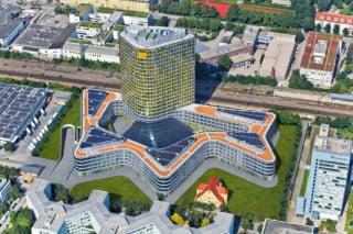 Die Luftaufnahme zeigt die PV-Anlage auf den fünf Flachdächern des Sockelbaus und den Schattenwurf des Turms auf das Bahngelände. Unten rechts im Bild die sanierte Jugendstilvilla Sander