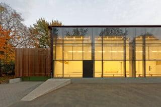 Die Sporthalle ist an drei Seiten von Nebenräumen eingefasst und orientiert sich mit ihren Verglasungen nach Nordwesten
