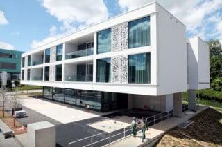 Das Gebäude wendet sich mit großflächigen Verglasungen der nahen, südlich gelegenen Kinderklinik zu