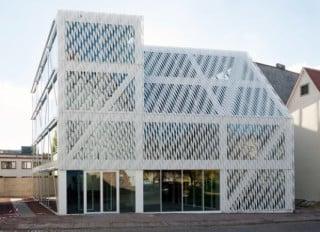 Das vorgelagerte Geflecht aus weißen Edelstahlprofilen bedeckt Fassade und Dach gleichermaßen