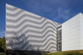 Die Versuchshalle ist von vertikalen Aluminiumprofilen eingehüllt, die in unterschiedlichen Abständen angebracht sind und unterschiedliche Muster entstehen lassen