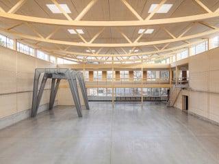 Die Werkhalle mit Holzschindelfassade und der verputzte Bürotrakt umfassen L-förmig den Hof (Ostansicht)