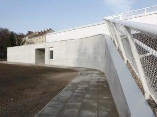 Zugang für die Sportler mit dem als Welle ausgebildeten Dach auf der Südfassade zu den Sportplätzen hin
