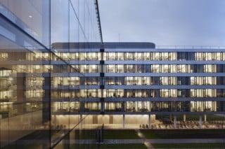 Glas und Edelstahlbrüstungen prägen die Fassaden der neuen Konzernzentrale, das EG wurde teilweise ausgespart und die fünf Obergeschosse auf Stelzen gestellt