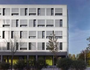 Südansicht: Die reflektierende, weiße Fassade der oberen Geschosse hebt sich deutlich vom dunklen Sockel ab