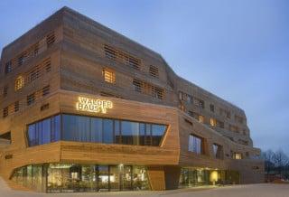 Westansicht am Abend: Ausstellungs- und Schulungshaus, Hotel und Restaurantbetrieb unter einem Dach