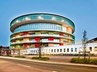 Ansicht von Norden: Der weithin sichtbare, siebengeschossige Baukörper bildet den Kopf des Gebäudebestands an der Durchfahrtstraße und begrenzt diese mit einem eingeschossigen weißen Riegel