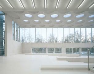 Die nüchterne Südfassade wurde im unteren Bereich mit Aluminiumpaneelen verkleidet, während die obere Hälfte komplett verglast ist