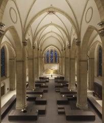 Ein symmetrischer Teppich aus dunklen, lang gezogenen Bronzequadern bedeckt den Boden des Kirchenmittelschiffs