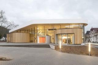 In die großflächig verglaste Fassade schieben sich zwei organisch geformte Baukörper, die mit sibirischem Lärchenholz verkleidet sind