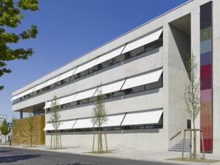 Je eine schmale, gebäudehohe Öffnung markiert den Eingang an beiden Flügeln des L-förmigen Gebäudes