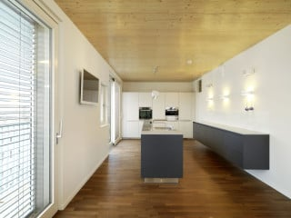 Mit seiner Fassade aus dunkelgrauen Faserzementtafeln bildet das Wohnhaus B26 einen starken Kontrast zu seinem weiß verputzten Nachbarn (Südostansicht)