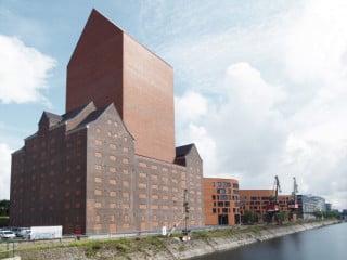 Der fensterlose Archivturm aus Klinkermauerwerk ragt aus dem unter Denkmalschutz stehenden, ehemaligen Getreidespeicher von 1936 am Innenhafen heraus