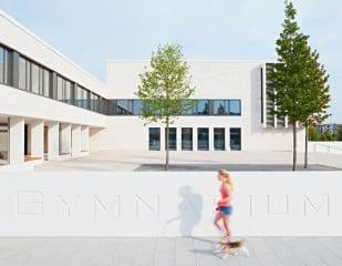 Das neue Gymnasium liegt im Zentrum von Frankfurt-Riedberg, der Haupteingang befindet sich an der Ostseite des Schulkomplexes (in der Abb. in der Gebäudeecke zwischen Aula, links, und Klassentrakt rechts)