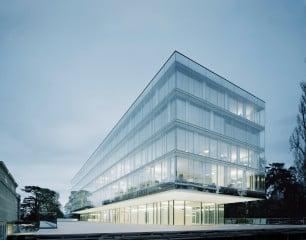 Der schmale Büroriegel wirkt offen und transparent, Decken und Attika verschwinden nahezu hinter einer doppelten Glasfassade