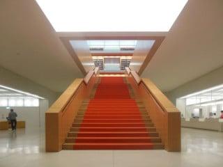 Vom kühl-weiß gehaltenen Foyer führt die zentrale Holztreppe in den Lesesaal