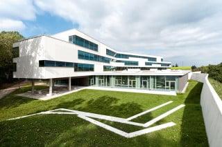 Ein polygonaler Grundriss, gefaltete Wandflächen und versetzt übereinander liegende Geschosse lockern den Baukörper auf und gliedern ihn, verzahnen ihn mit der Umgebung und definieren unterschiedliche Außenbereiche