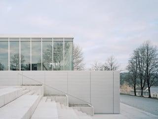 Das Forum ist teilweise im ansteigenden Gelände eingegraben: im Vordergrund ist die Treppe zum oberen Eingang zu sehen, dahinter der schmale Baukörper mit Foyer und Haupteingang sowie die große Halle im Hintergrund (Westansicht)