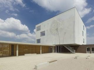 Ein textiler Fassadenscreen umhüllt die drei Obergeschosse und lässt den an mehreren Stellen eingeschnittenen Baukörper als ruhigen Quader erscheinen