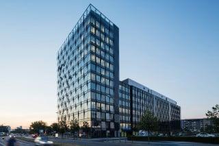 Wie ein leichtes Flechtwerk zieht sich die Glasfassade über den Neubau an der Mühlenstraße