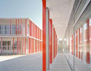 Die Schule ist wesentlich geprägt durch umlaufende Aluminiumlamellen, die in einem freien Rhythmus zwischen den schmalen Betondecken aufgespannt sind und die Struktur der Quader stark auflockern