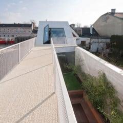 Das langgestreckte, weiße Patiohaus nimmt die gesamte Grundstücksfläche ein und variiert zwischen einem und zwei Geschossen