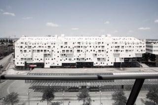 Der insgesamt 110 Meter lange Bau erstreckt sich entlang der Hauptverkehrsstraße, vorgelagert im Bild die Überdachung der U-Bahnstation Kagraner Platz mit Busterminal