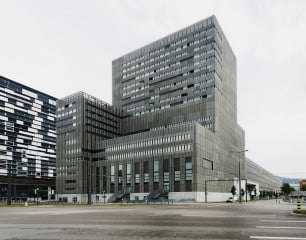 Ansicht von der Pfingstweidstraße: Die turmartige Aufstockung beherbergt Wohnungen mit Blick über die ganze Stadt