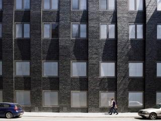 Die neue titangrau schimmernde Klinkerfassade vermittelt zu den umgebenden Bauten aus Sichtmauerwerk ebenso wie zu den aluminiumverkleideten