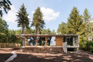Die Südfassade öffnet sich mit einer Glasfront zum See und wird von dünnen Betonscheiben gerahmt