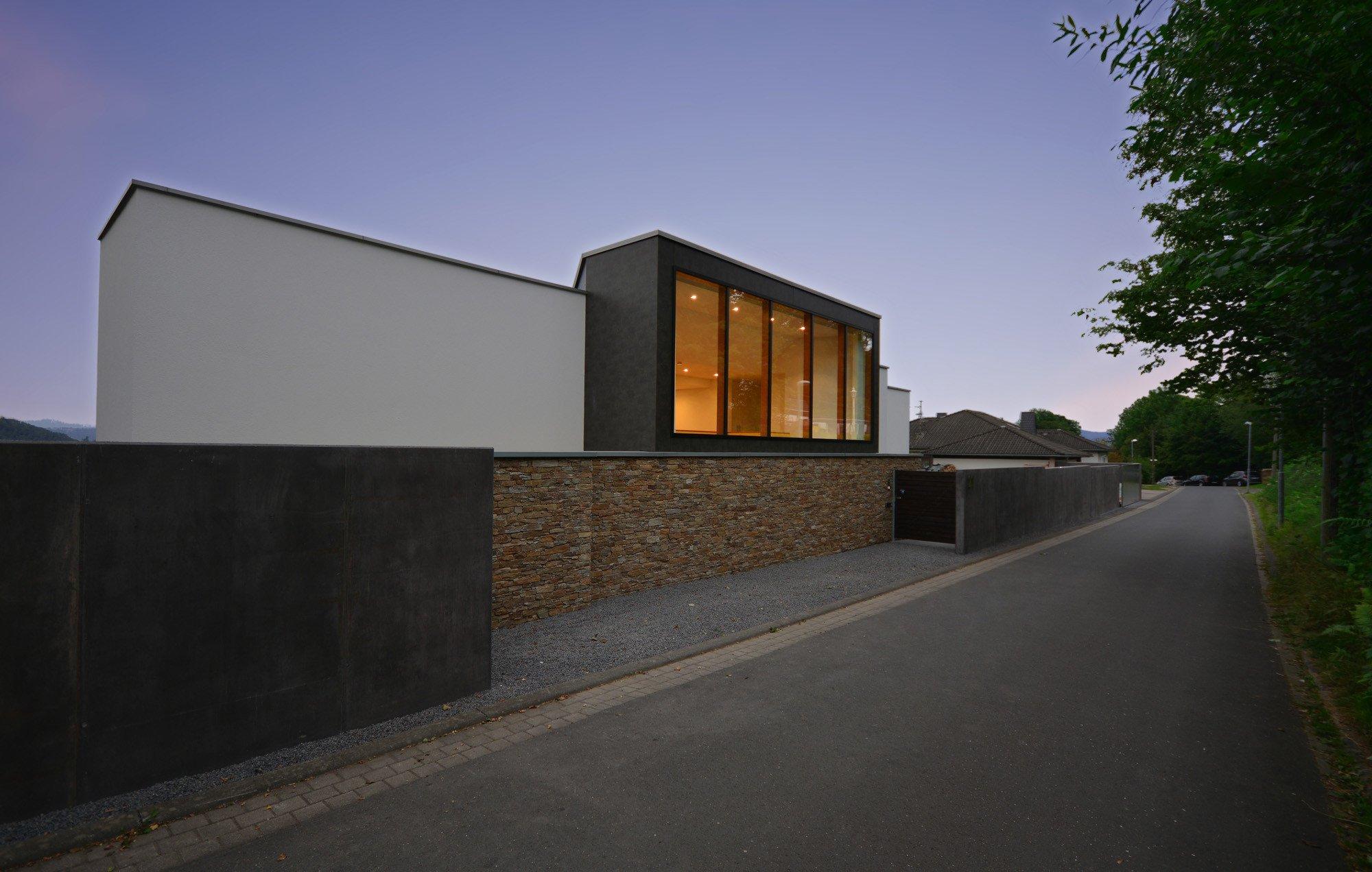 Kontraste In Der Zur Straße Zeigenden Südfassade Aus Hellem Und Dunklem  Sichtbeton Und Bruchsteinmauerwerk