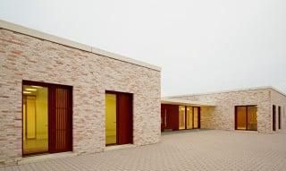 Krippe und Mensa sind in zwei eigenen, eingeschossigen Baukörpern untergebracht  und stehen leicht versetzt zueinander; beide haben Fassaden aus hellem Sichtmauerwerk