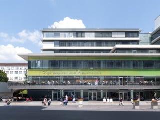 Der Sockelbau hebt sich mit grün hinterlegten Gussglasscheiben von den weißen Alu-Fassadenpaneelen der Bettenhäuser darüber ab (Südostansicht mit Cafe und Haupteingang, ganz rechts)
