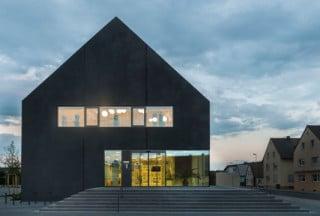 Die Erweiterung beherbergt im Obergeschoss einen großen Ratssaal und bildet den neuen Eingang des Gemeindezentrums