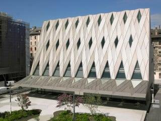 Über das hoch aufragende Volumen des neuen Eingangsgebäudes des Museums legt sich eine Metallverkleidung aus eloxierten Aluminiumblechen wie ein scharfkantig gefalteter Teppich