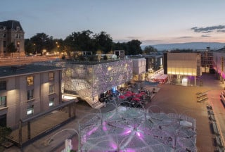 Das mit einem Fassadengitter verkleidete Haus C ist das bedeutendste Gebäude der Reihe und öffnet sich zum Platz hin mit einem Cafe