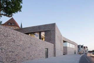 Wie ein Böschungsbauwerk steht das Europäische Hansemuseum am Fuß des Lübecker Burghügels