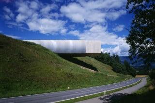 Ansicht Südwest: Auf einem Hügel etwas abgerückt von der Gemeinde kragt ein Betonriegel weit aus