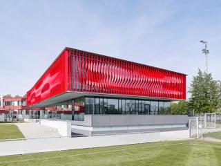 Der zeichenhafte Bau des neuen Jugendleistungszentrum ist im Obergeschoss von leuchtend roten Lamellen umhüllt (Ansicht Nordost)