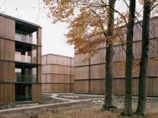 E2A Architekten schufen ein durchgrüntes Gefüge viergeschossiger Quader, die in lockerer Reihung den Straßenraum fassen (Ansicht von der Kurfirstenstraße)