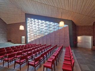 Den großen Saal der Johanneskirche prägen die Lichtwand sowie die Schieferbodenplatten, das Ziegelmauerwerk und die hölzerne Dachuntersicht