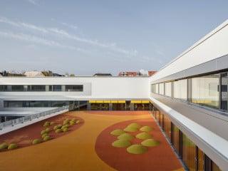 Eine Hälfte des Schulpausenhofes ist erhöht: Das Dach der Sporthalle wird zur Spielfläche, die von den Gruppenräumen des Hortes aus zugänglich ist