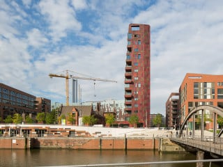 Der dunkelrot changierende Cinnamon Turm im Hamburger Überseequartier ragt neben dem denkmalgeschützte Alten Hafenamt zeichenhaft in die Höhe