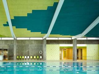 Markant an dem für die 1970er-Jahre typischen Gebäude ist das asymmetrische Dach der Schwimmhalle