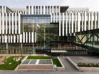 An der Eingangsseite im Nordwesten bricht die Fassadenstruktur großflächig auf: Dort öffnet sich das Forschungsinstitut transparent über fünf Geschosse und lässt tiefe Einblicke ins Atrium als dem kommunikativen Herzstück zu