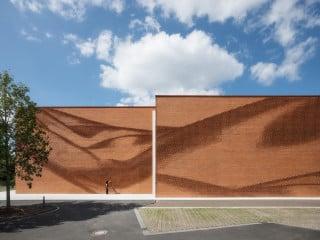 Die Ziegelfassade des Neubaus für den Verband der Nordwestdeutschen Textil- und Bekleidungsindustrie in Münster bildet den fließenden Faltenwurf eines gigantischen Tuches nach