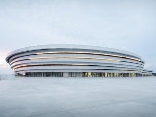 Inmitten offener Landschaft und nahe der Autobahn zieht die Arena du Pays d'Aix mit einer bandartig geschwungenen Aluminiumfassade die Blicke auf sich